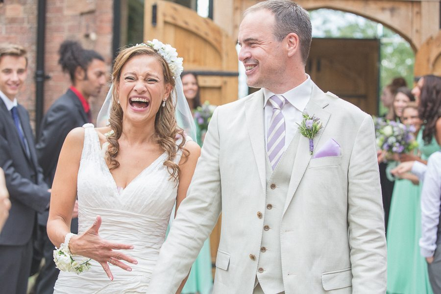 Bride and groom laughing widely down the aisle