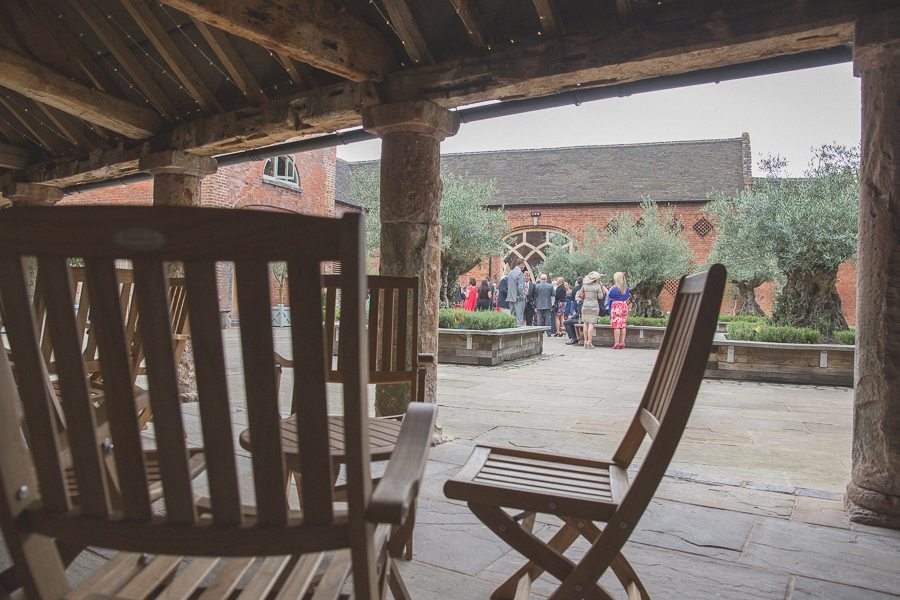 Wedding guests chatting in the grounds of Shustoke Farm Barns