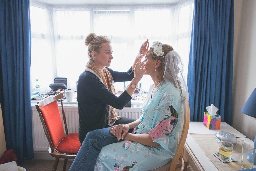Bride's make up being done for her Shustoke Farm Barn wedding