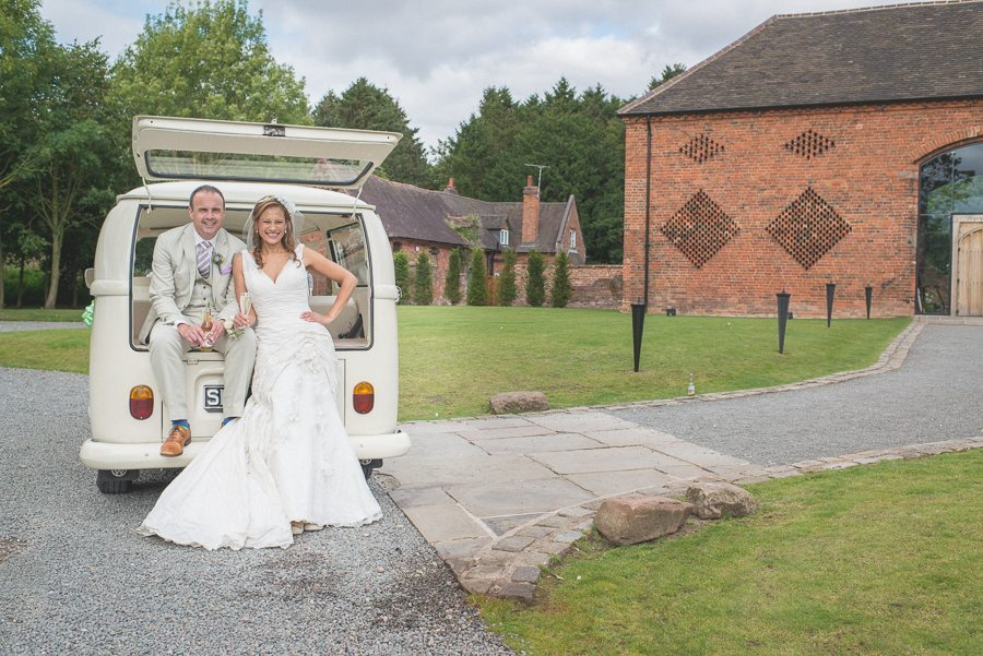 Bride and groom smiling at their VW wedding van in front of Shustoke Farm Barns
