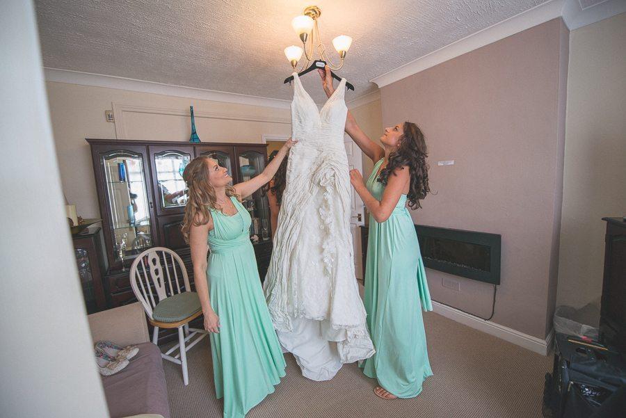 Bridesmaids hanging up the bride's dress