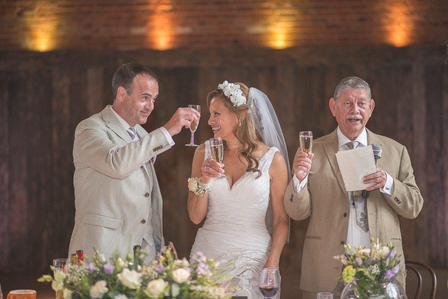 Bride and Groom cheersing their guests at Shustoke Farm Barns