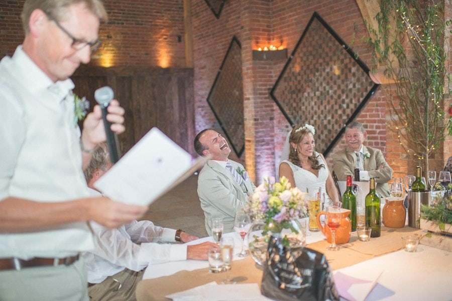 Bride and groom laughing loud during the best man's speech