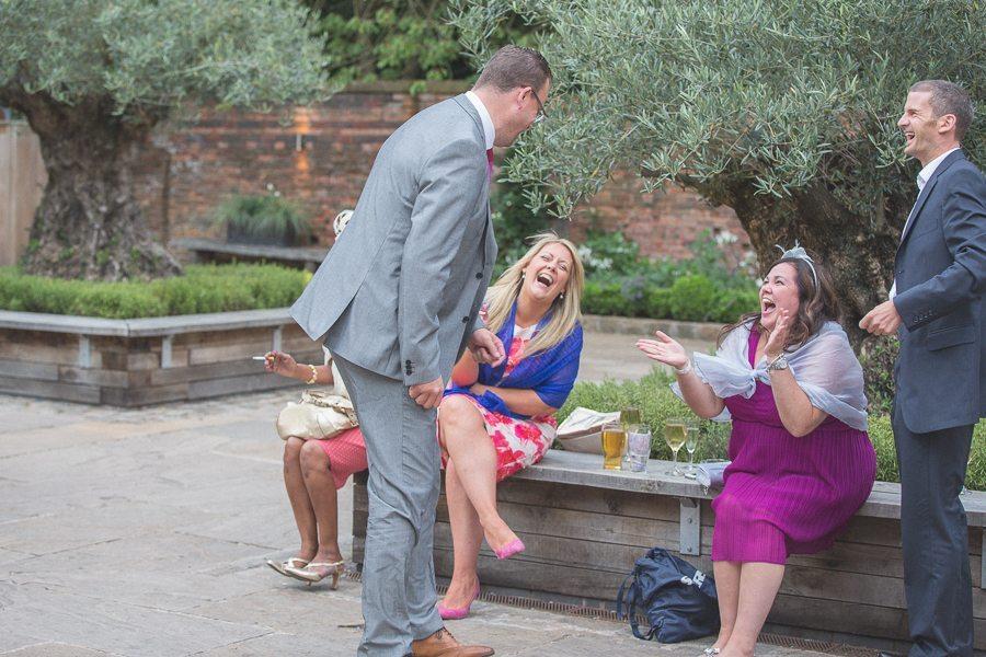 Wedding guests laughing at Shustoke Farm Barns