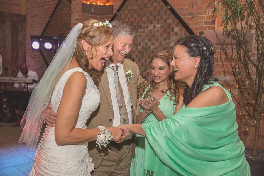 Bride laughs with her bridesmaids dressed in mint green bridesmaids dresses