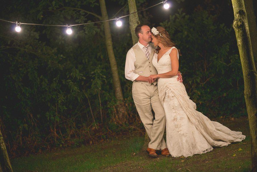 Bride and groom kuddling under pontoon lights at Shustoke Farm Barns
