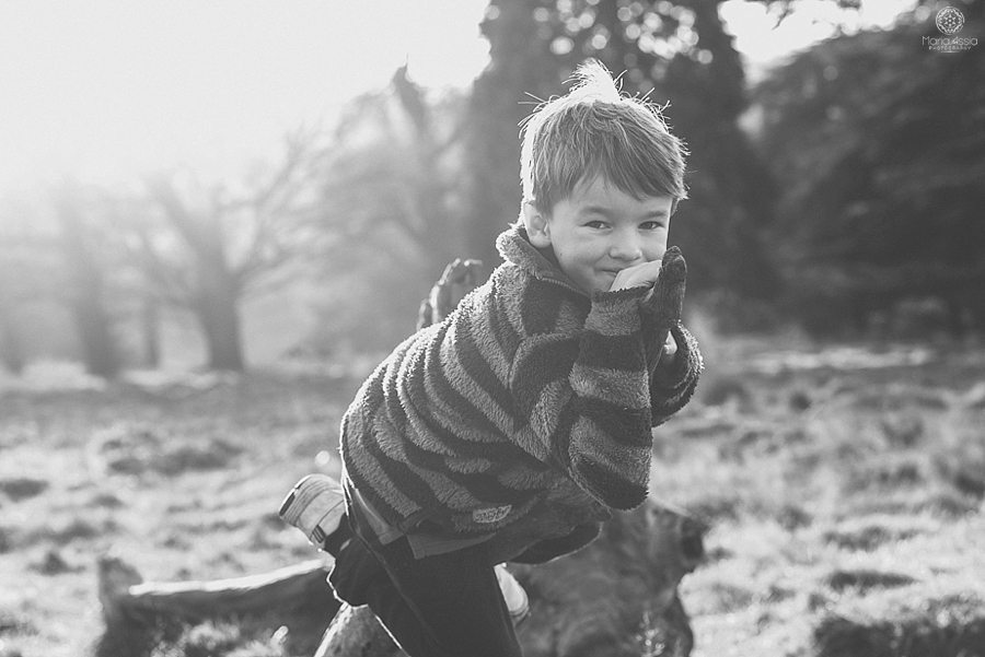 Boy lying on a tree stump at Pembroke Lodge