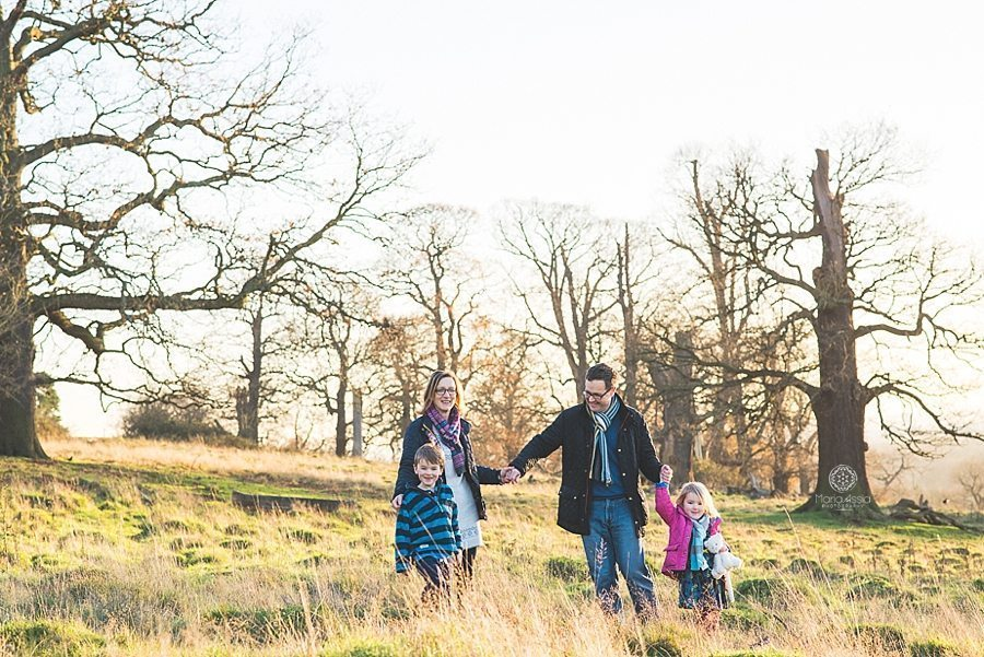 Family with two small children walking through the tall grass in Richmond Park