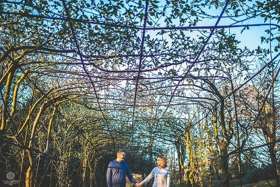 engaged couple holding hands at their Pembroke Lodge winter pre-wedding photo shoot by alternative wedding photographer Maria Assia Photography