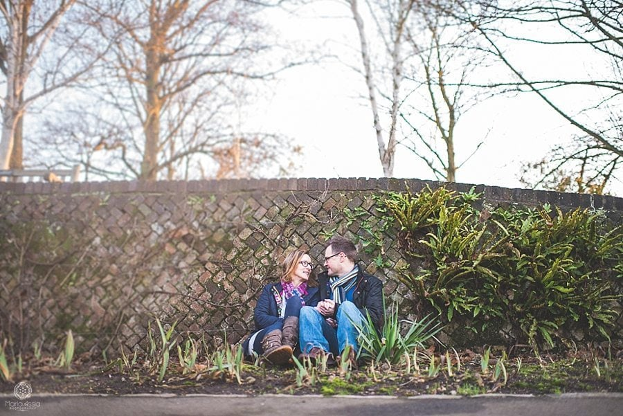 engaged couple sitting against a paved wall at Pembroke Lodge winter pre-wedding photo shoot with a sunflare
