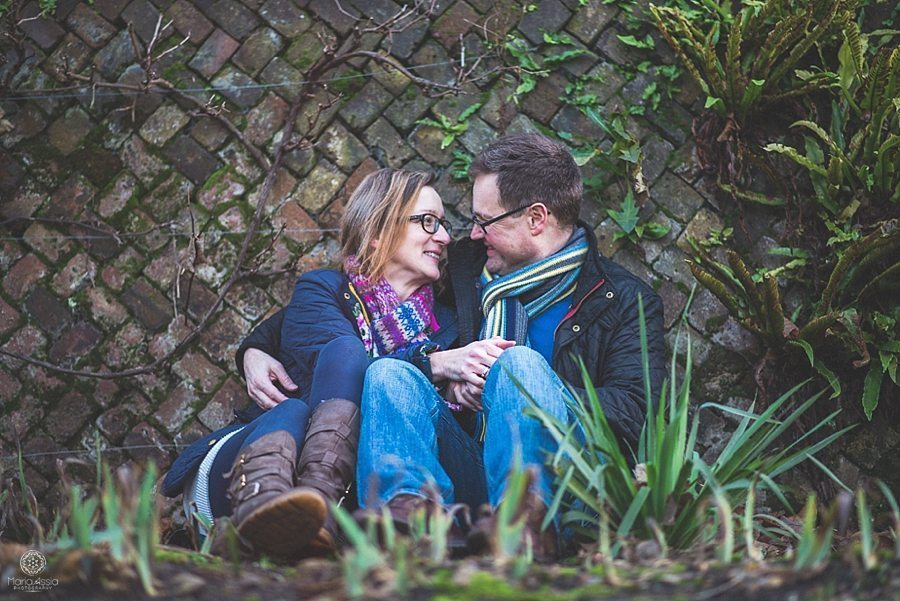 Engaged couple sitting against a paved wall at Pembroke Lodge winter pre-wedding photo shoot