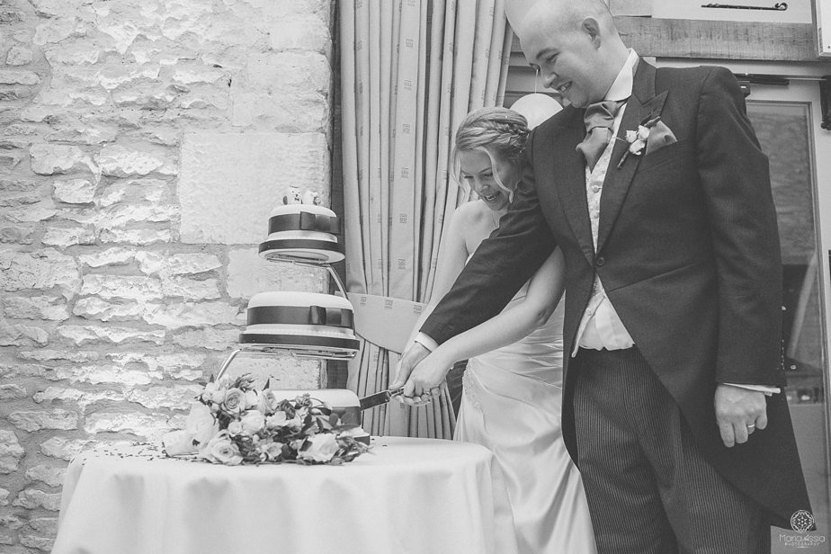 Bride and Groom cutting their three tiered wedding cake at Caswell House purple themed autumn wedding