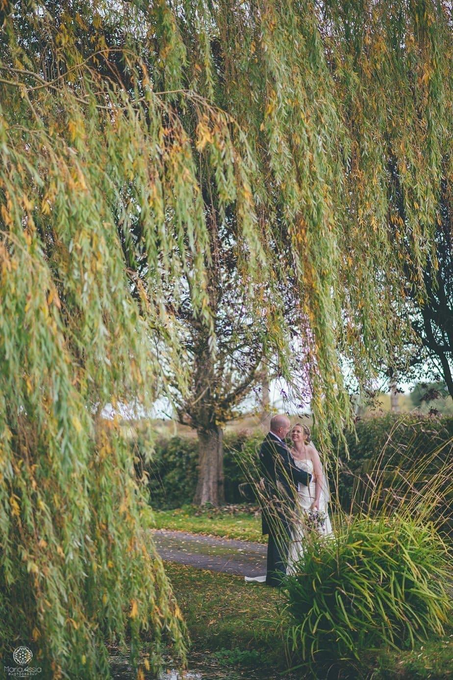 Bride and Groom hugging standing below a weeping willow
