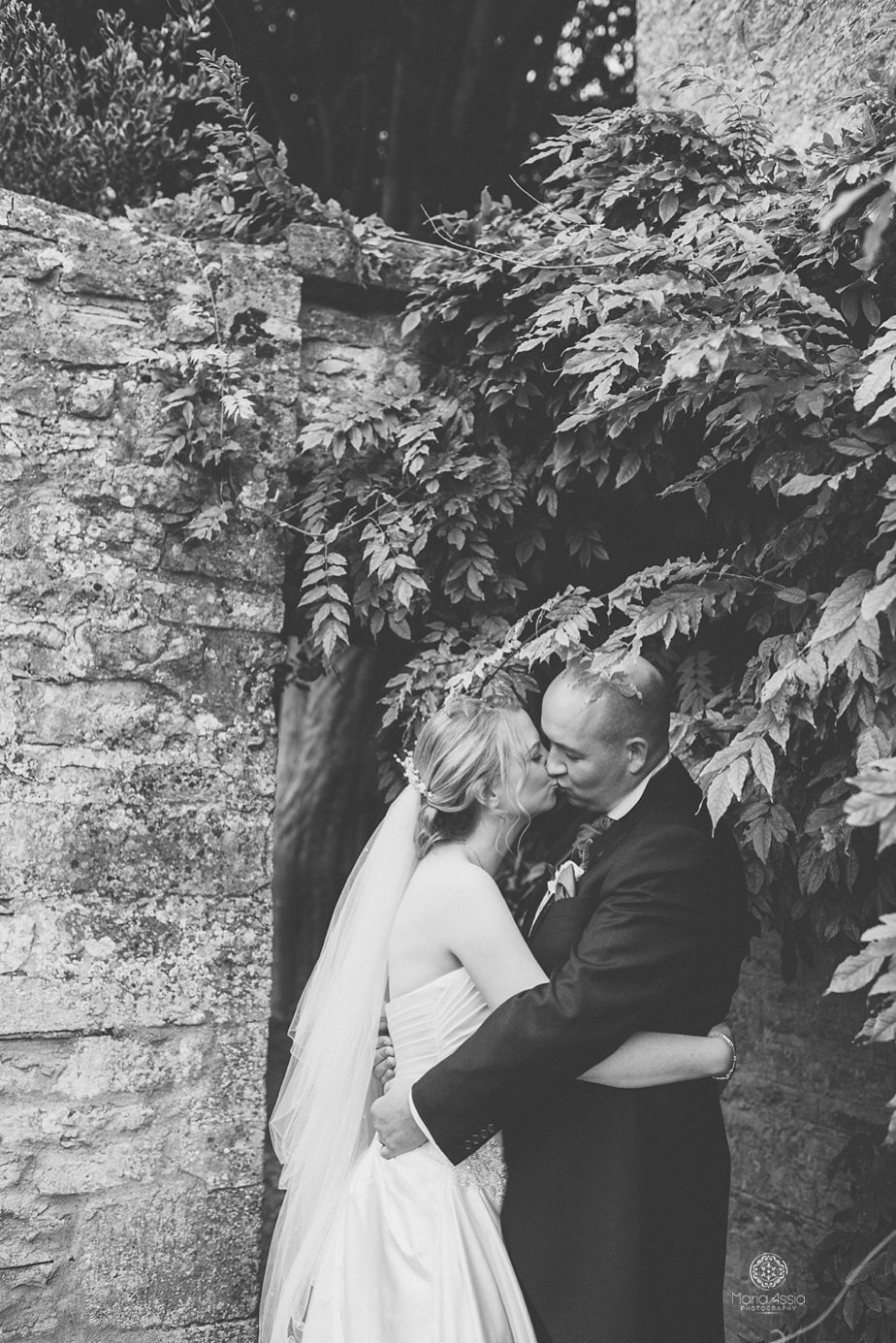Bride and groom kissing below wisteria leaves at Caswell House purple themed autumn wedding