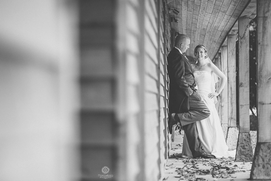Bride and groom leaning against a wooden wall at Caswell House