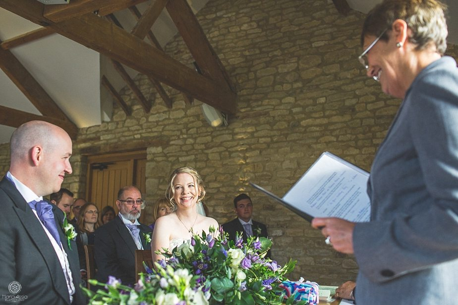 Bride and groom smile at each other while their registrar marries them at their Purple Themed Autumn Wedding