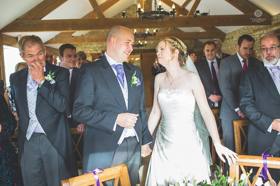 Bride and groom smiling at each other at the altar at Caswell House