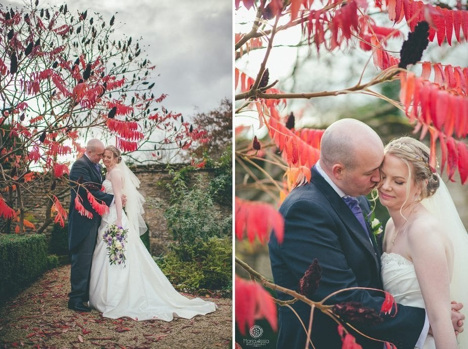 Caswell House Purple Themed autumn Wedding Bride and groom standing in red autumn foliage leaves