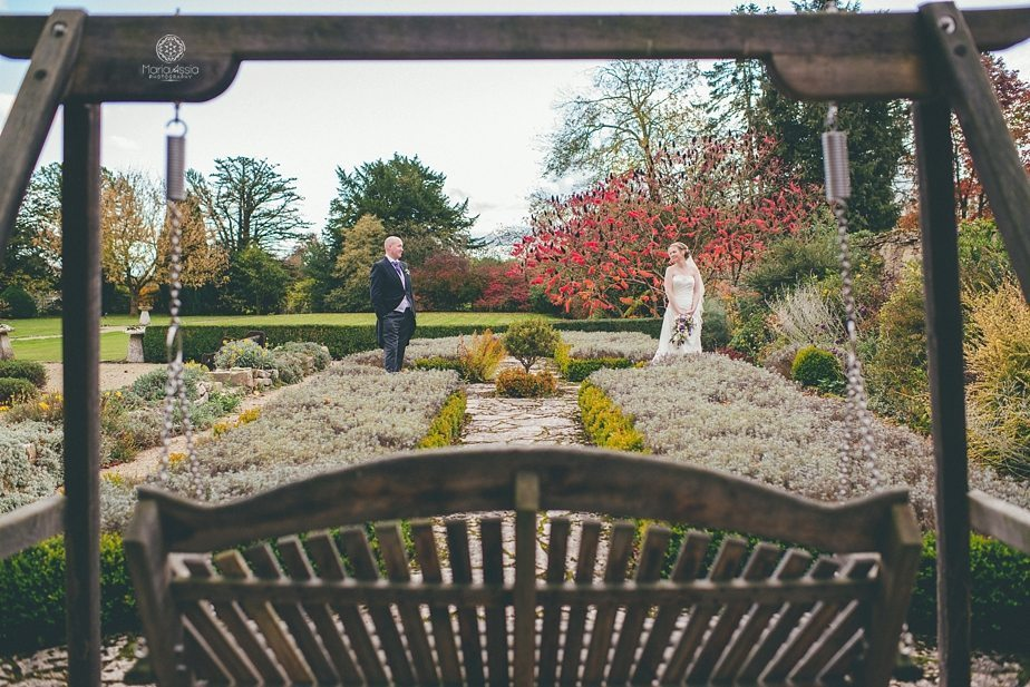 Caswell House Purple Themed Autumn Wedding Bride and groom standing in the grounds framed by the garden swing