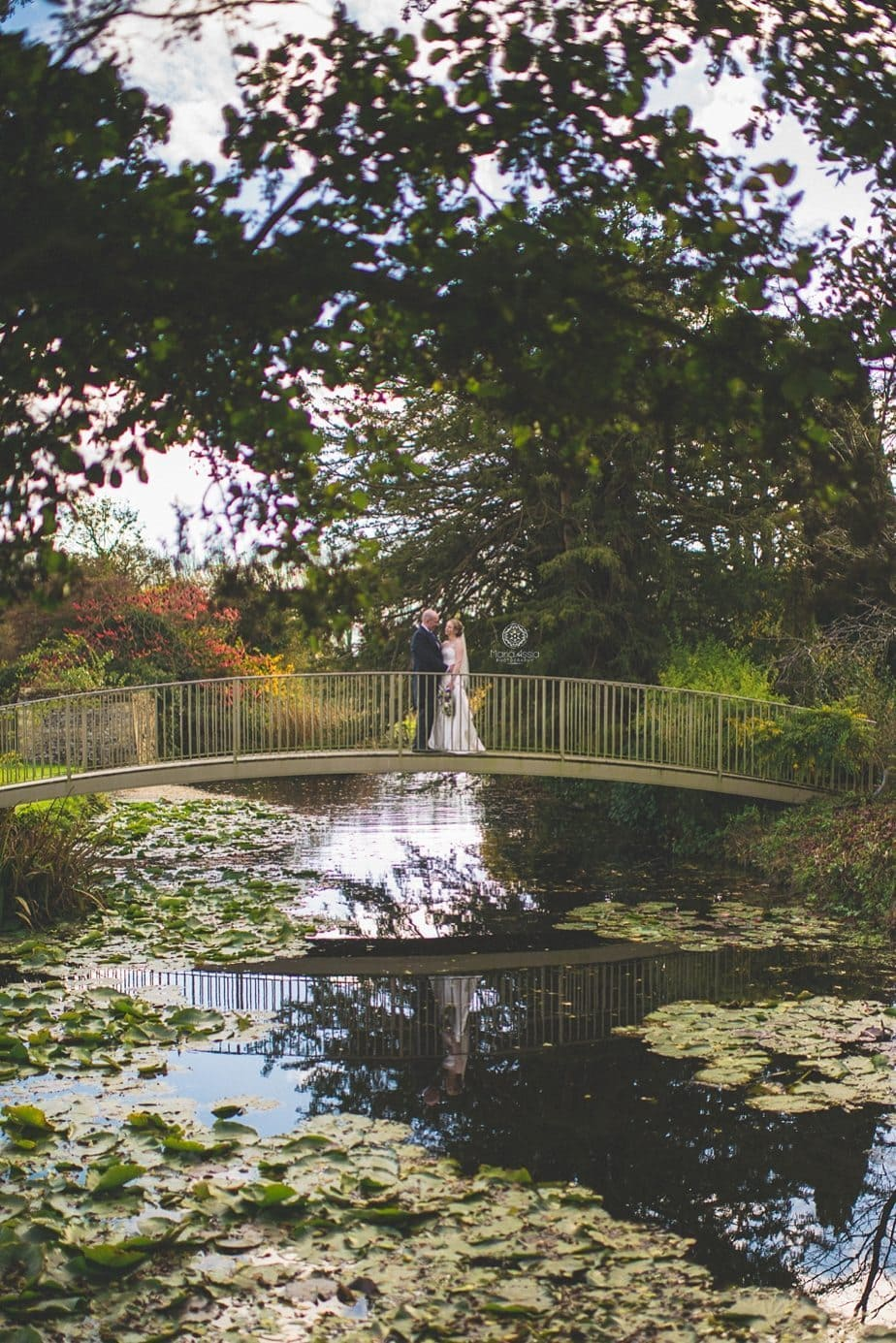 Bride and groom standing on the footbridge at Caswell House