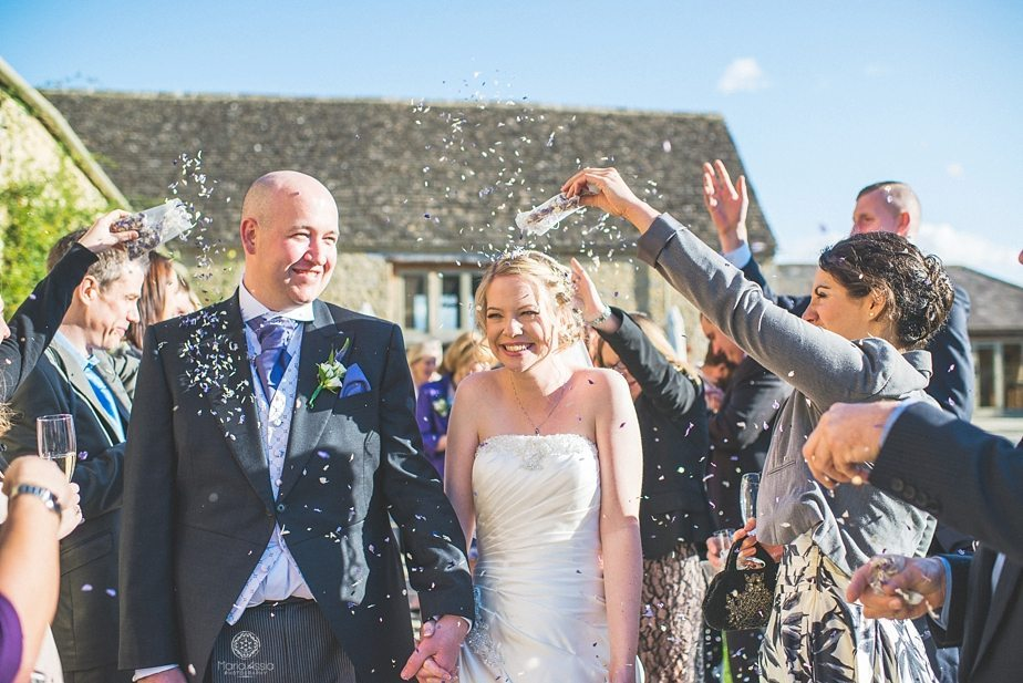 Bride and groom walking through confetti at Caswell House Purple themed autumn wedding