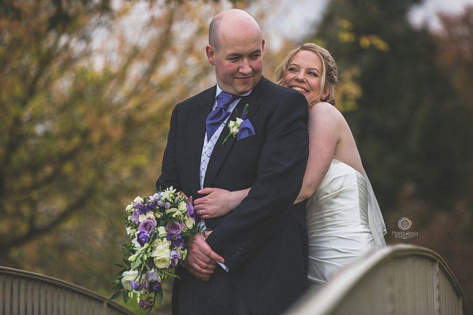Bride hugging her groom at Caswell House footbridge