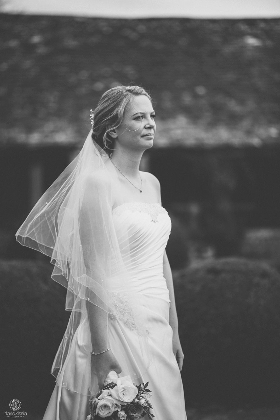 Bride looking over the gardens at her Caswell House purple themed autumn wedding