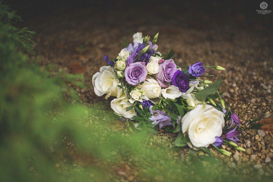 Purple themed autumn wedding Flowers lying on pebbled ground