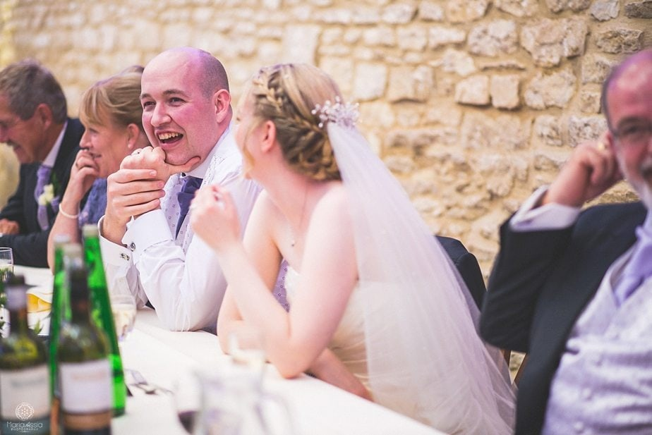 Groom laughing at his best man's speech at purple themed autumn wedding at caswell house