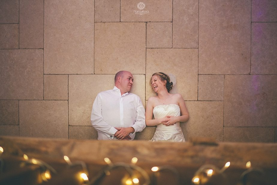 Purple themed autumn wedding Laughing Bride and groom lying below a balcony at Caswell House