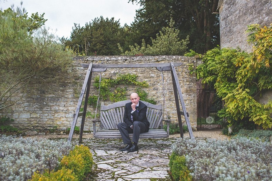Caswell House Groom sitting on the garden swing