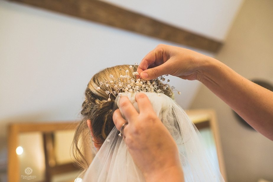 The wedding comb and veil being fitted into the bride's hair at Caswell House bridal suite