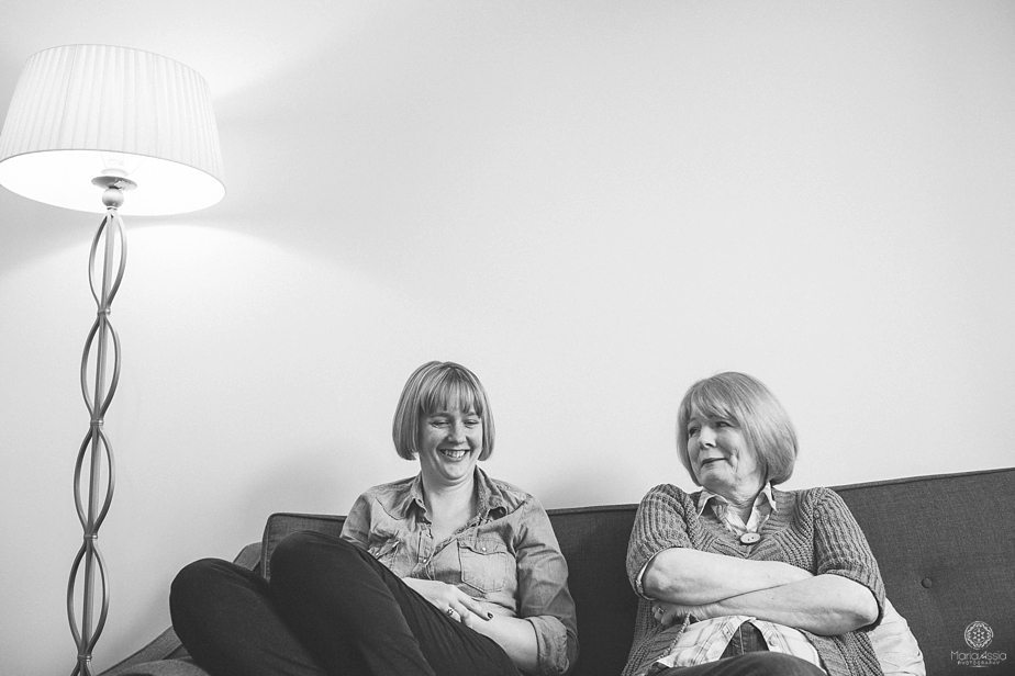 Two laughing women sitting on the couch