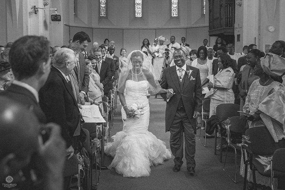 Bride and father of the bride smiling as they walk down the aisle at Christ Church in Winchester