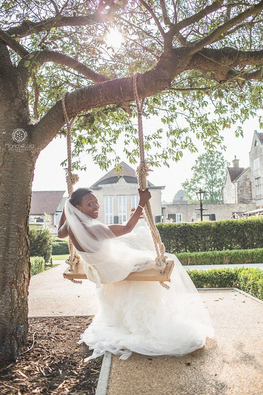 Bride sitting on the swing at Froyle Park
