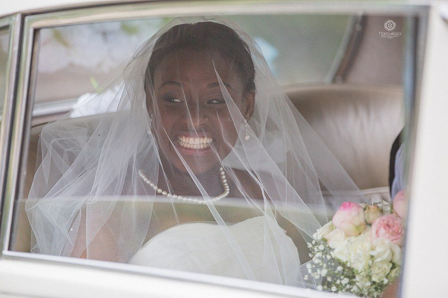 Colourful Ethnic Wedding Bride smiling at her guests from her classic car