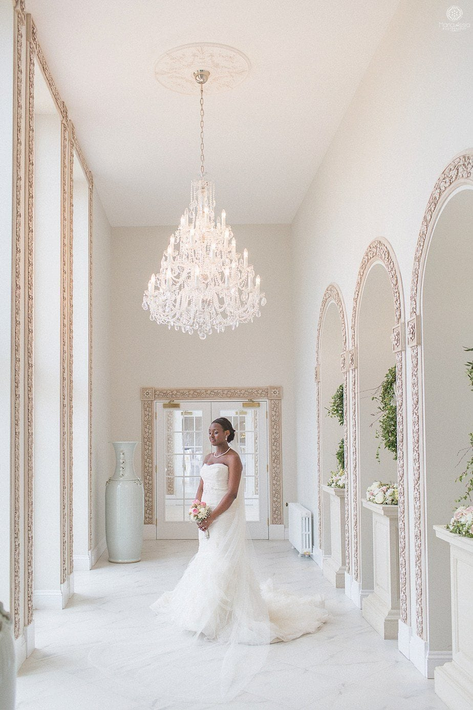 Colourful Ethnic Wedding bride standing below the chandelier at her Froyle Park wedding