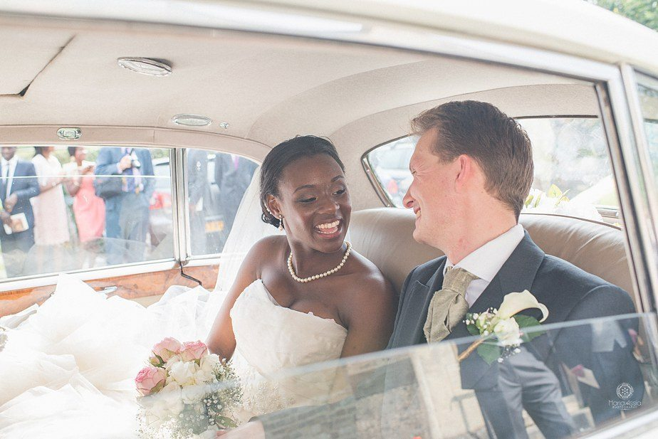 Colourful Ethnic wedding bride and groom smiling at each other in their classic car