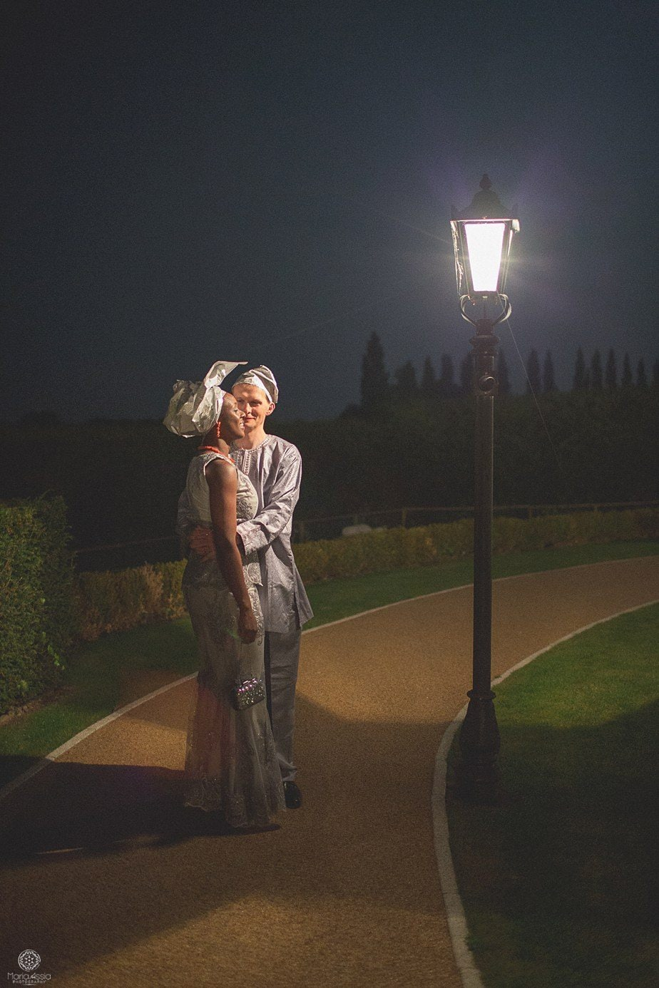 Colourful Ethnic wedding couple standing under a lamppost nightshot using creative lighting at Froyle Park