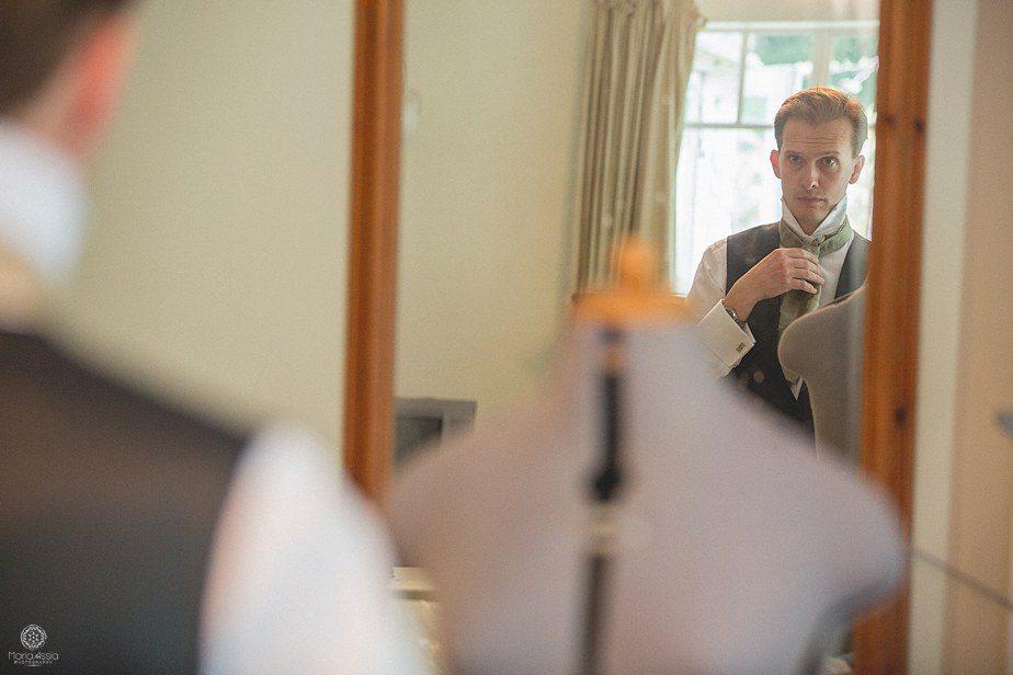 Groom fixing his tie in the mirror