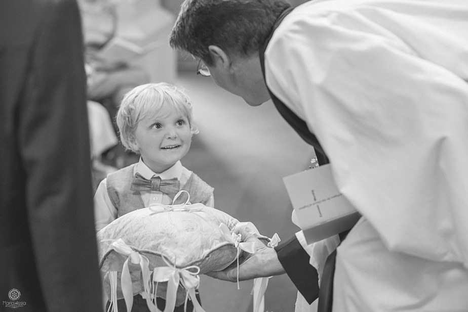 Vicar taking the wedding rings from a little boy ring bearer