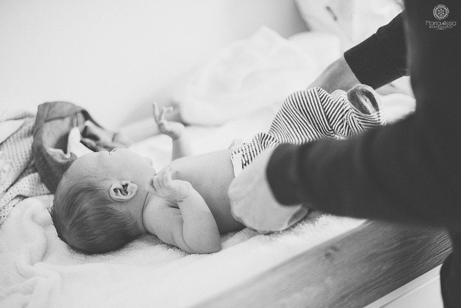 a father dressing his newborn son on the changing table