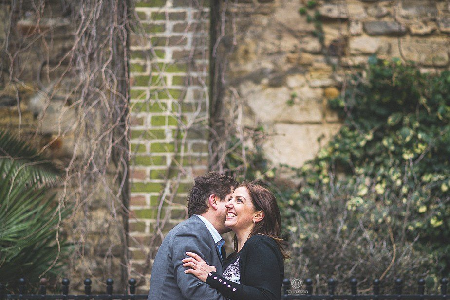 A couple hugging in a Hasting square on their engagement photo shoot