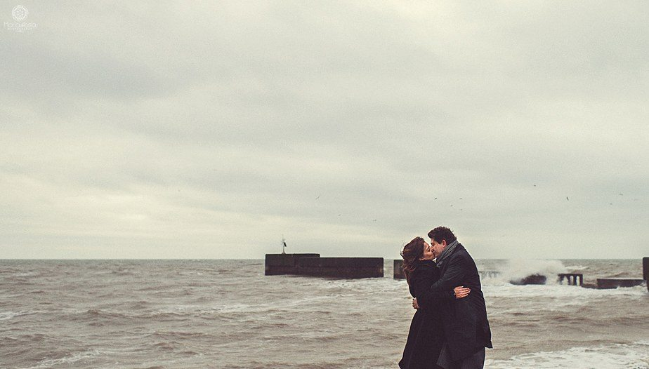 A couple kissing on the beach with the waves crashing into an old pier at their Hastings engagement photo shoot