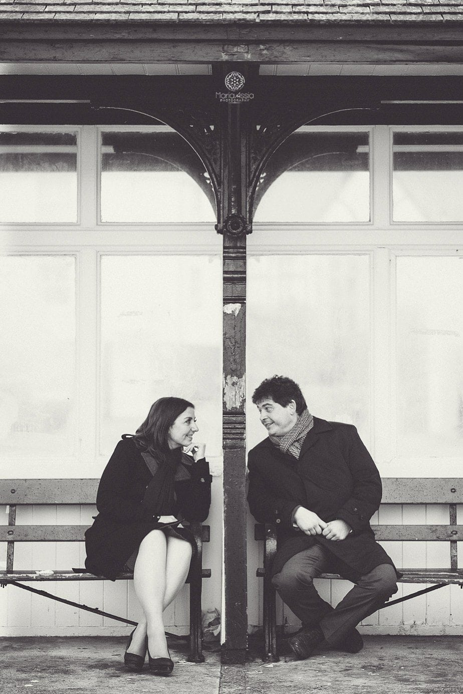 A couple looking and smiling at each other through the glass pane at a bus stop on their engagement photo shoot in Hastings