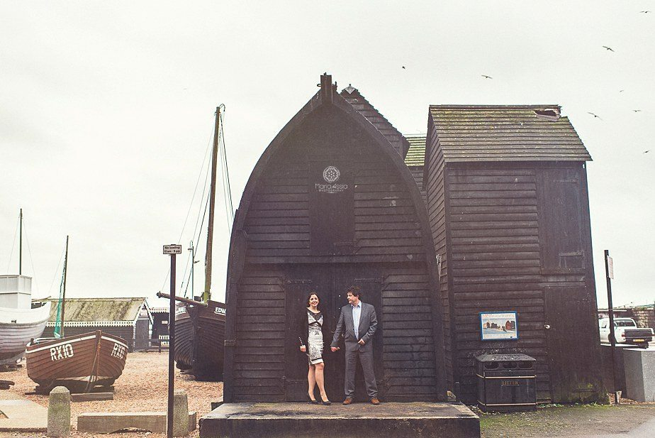 A couple standing in front of a black fishing hut at their Hasting engagement photo shoot