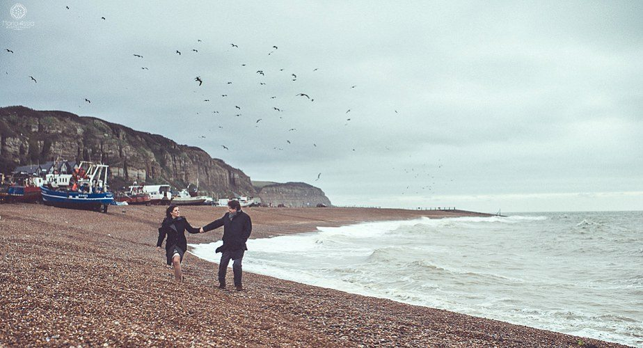A couple walking along a windy beach at their Hastings pre wedding shoot