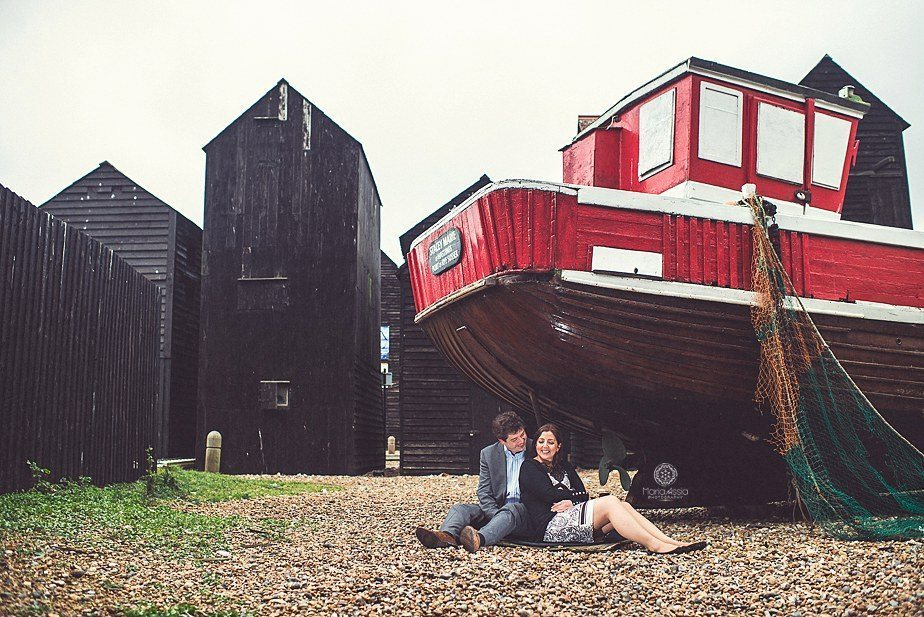An engaged couple sitting under a fishing boat surrounded by old black fishing huts on their Hastings pre wedding shoot