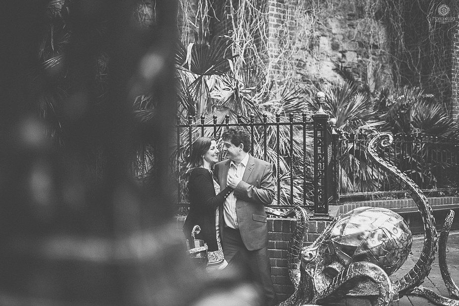Black and white photo or a couple hugging by a giant octopus statue in Hastings Old Town