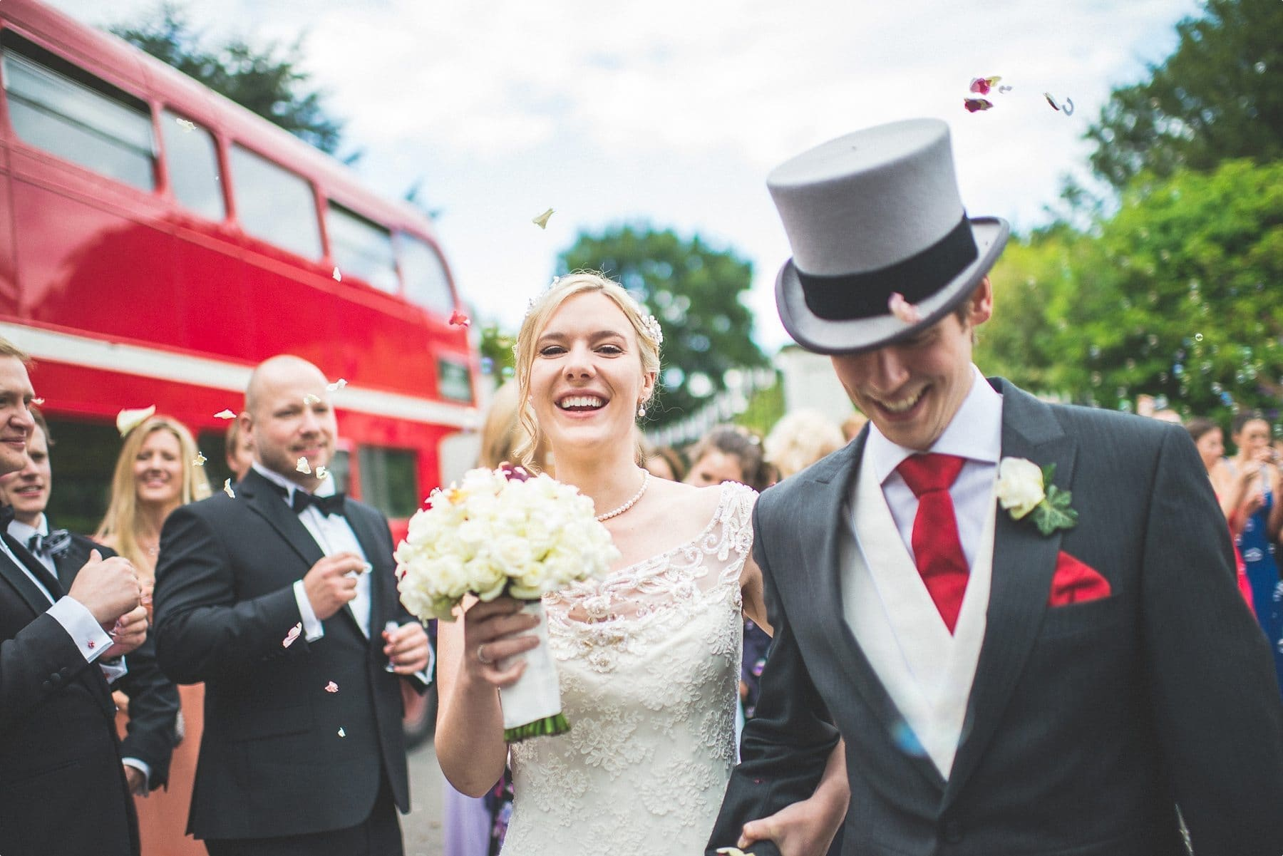 Bride and groom laughing and walking through their bubble and petal wedding confetti